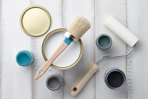 Paint brushes & a paint roller set up before an interior paint job