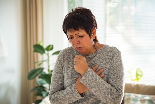 a woman coughing as an example of mold exposure